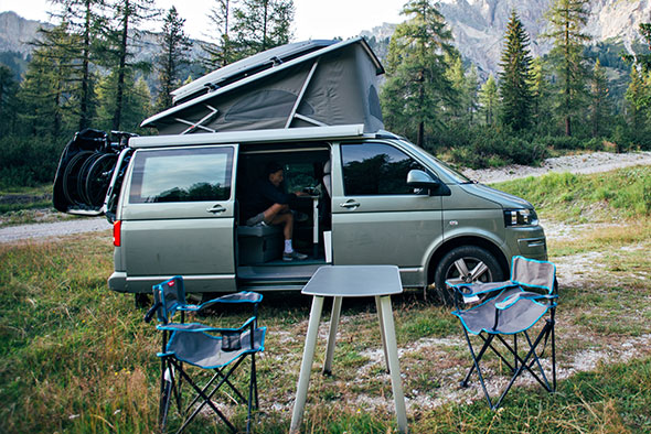 Green VW Campervan with table and chairs in woodland