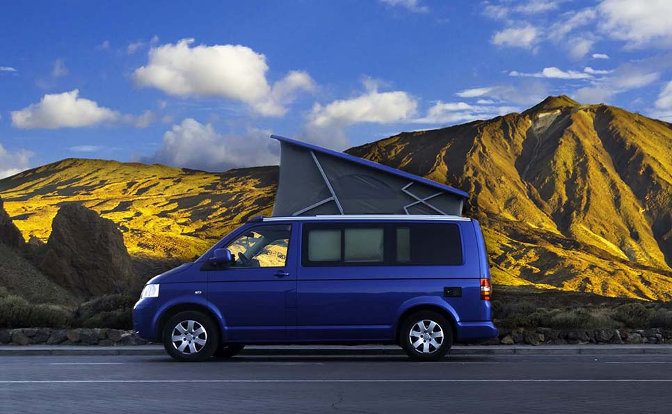 VW Campervan parked in front of mountains