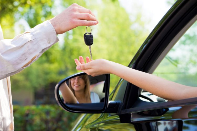 Man handing keys to woman in motorhome